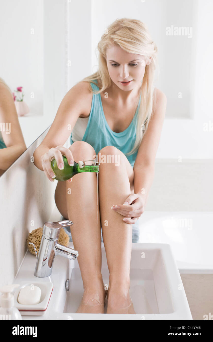 woman soaking feet in oil - Stock Image