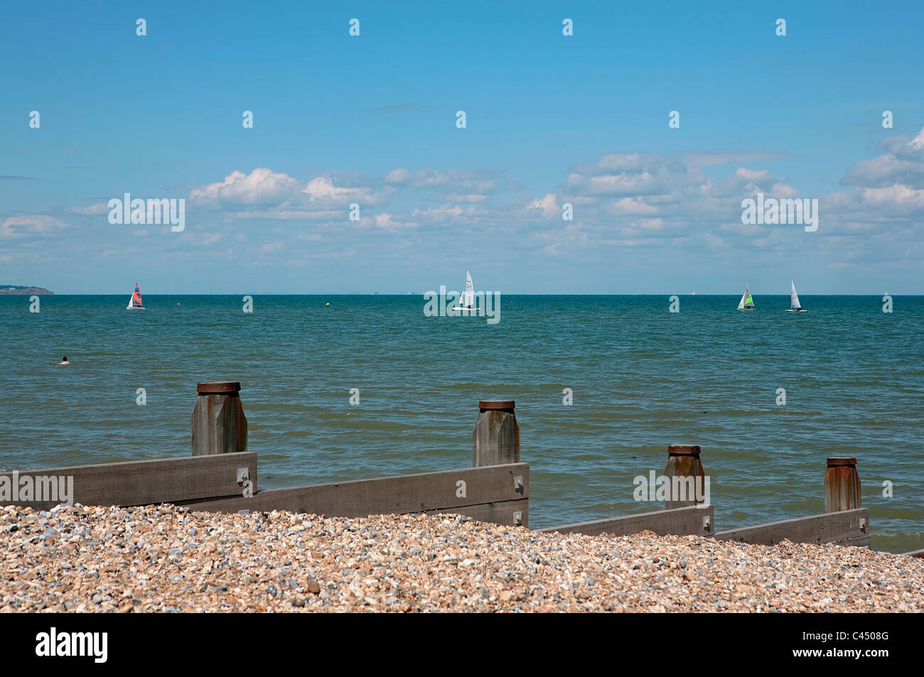 UK, England, Kent, Whitstable, view of sea with breakwaters, sailboats in background - Stock Image