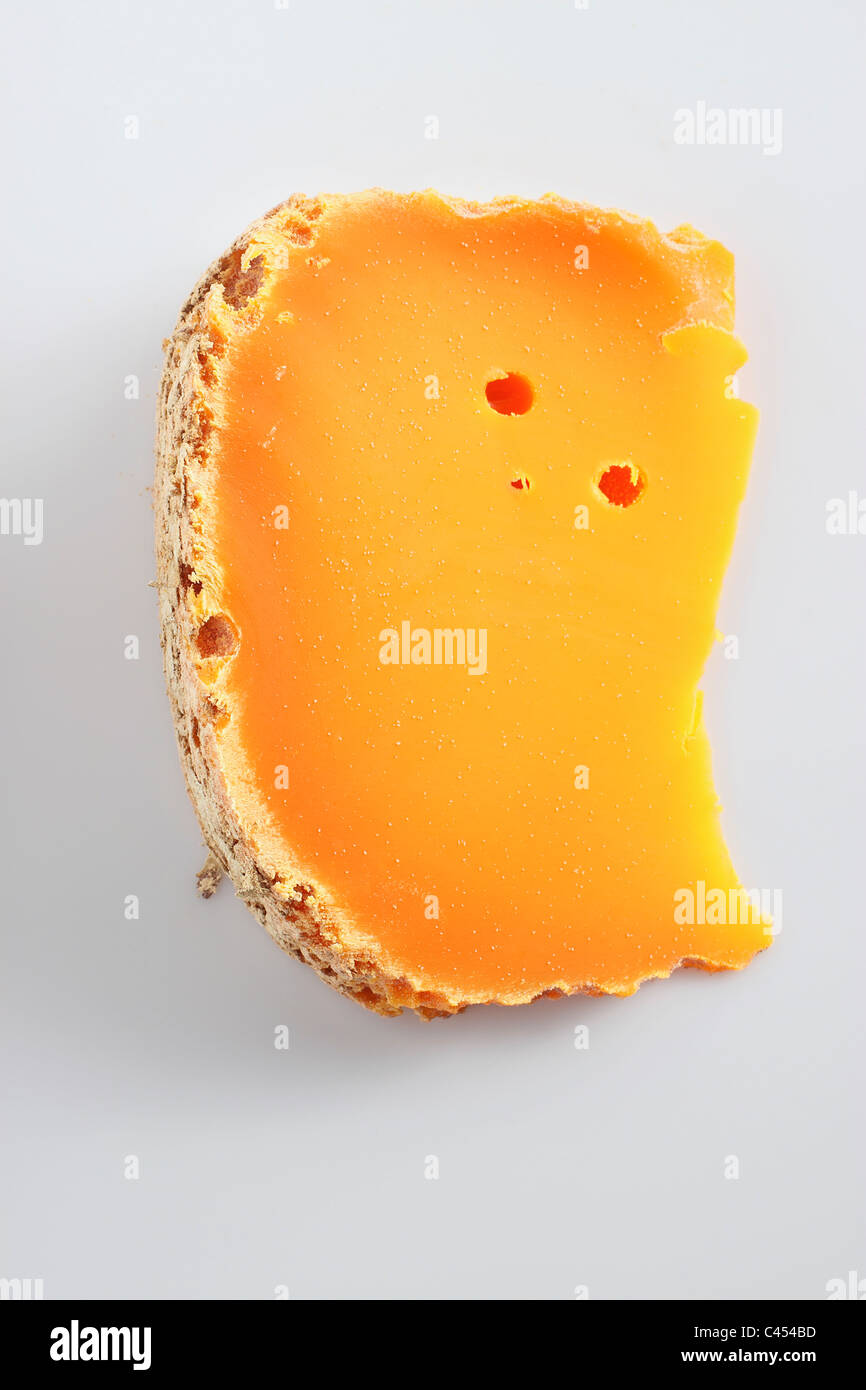 Slice of French Mimolette cow's milk cheese, close-up - Stock Image