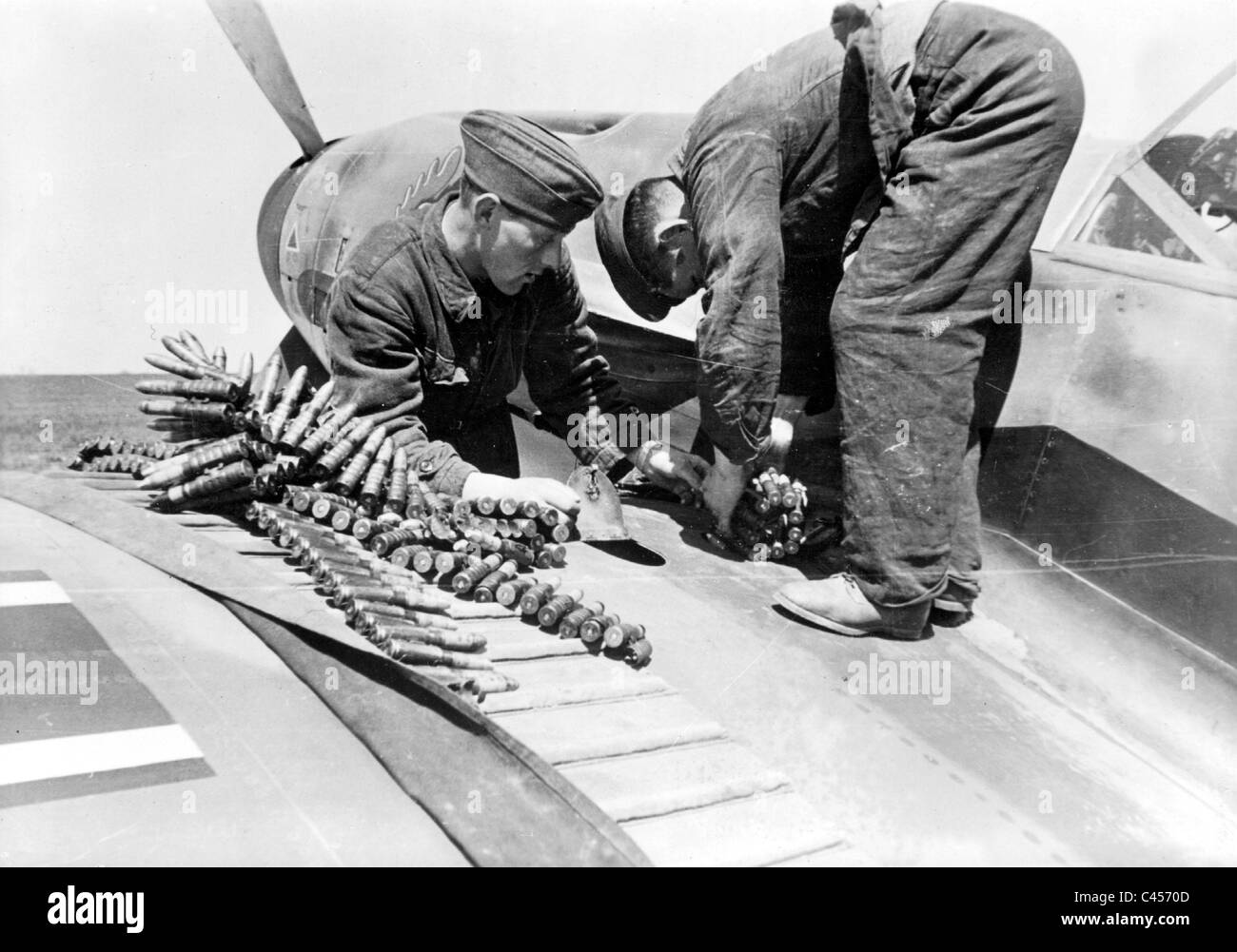 Ground crew reload ammunition in a fighter plane, 1942 - Stock Image