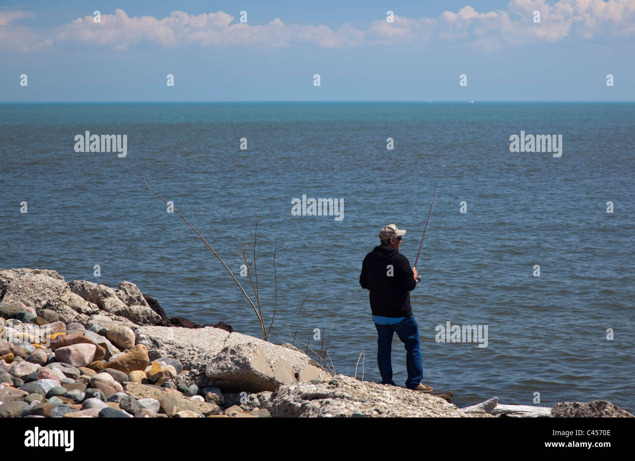 Harrison Township, Michigan - A man fishes from shore on Lake St. Clair. - Stock Image