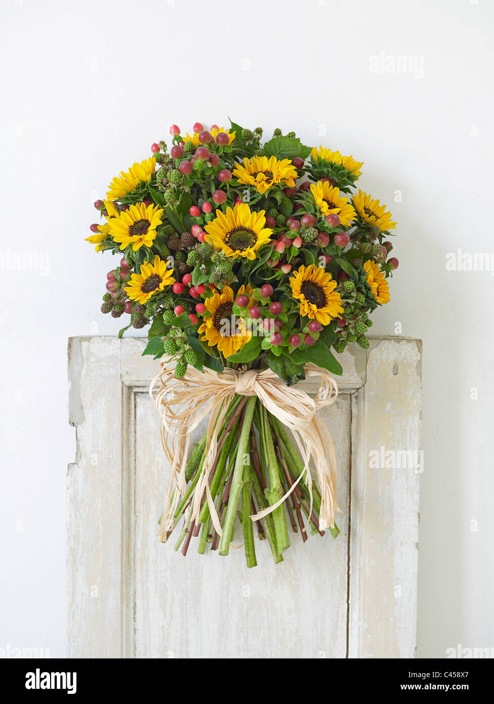 Bunch of flowers including sunflowers and berries, close-up - Stock Image