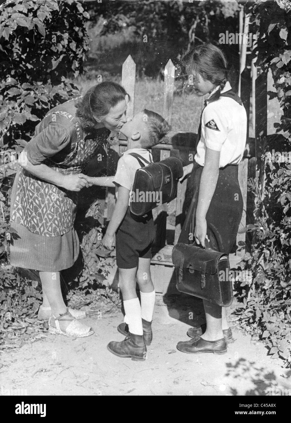 A mother says goodbye to her children as they go to school, 1943 - Stock Image