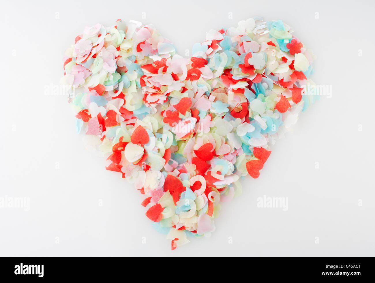 Heart shape formed with confetti, close-up - Stock Image