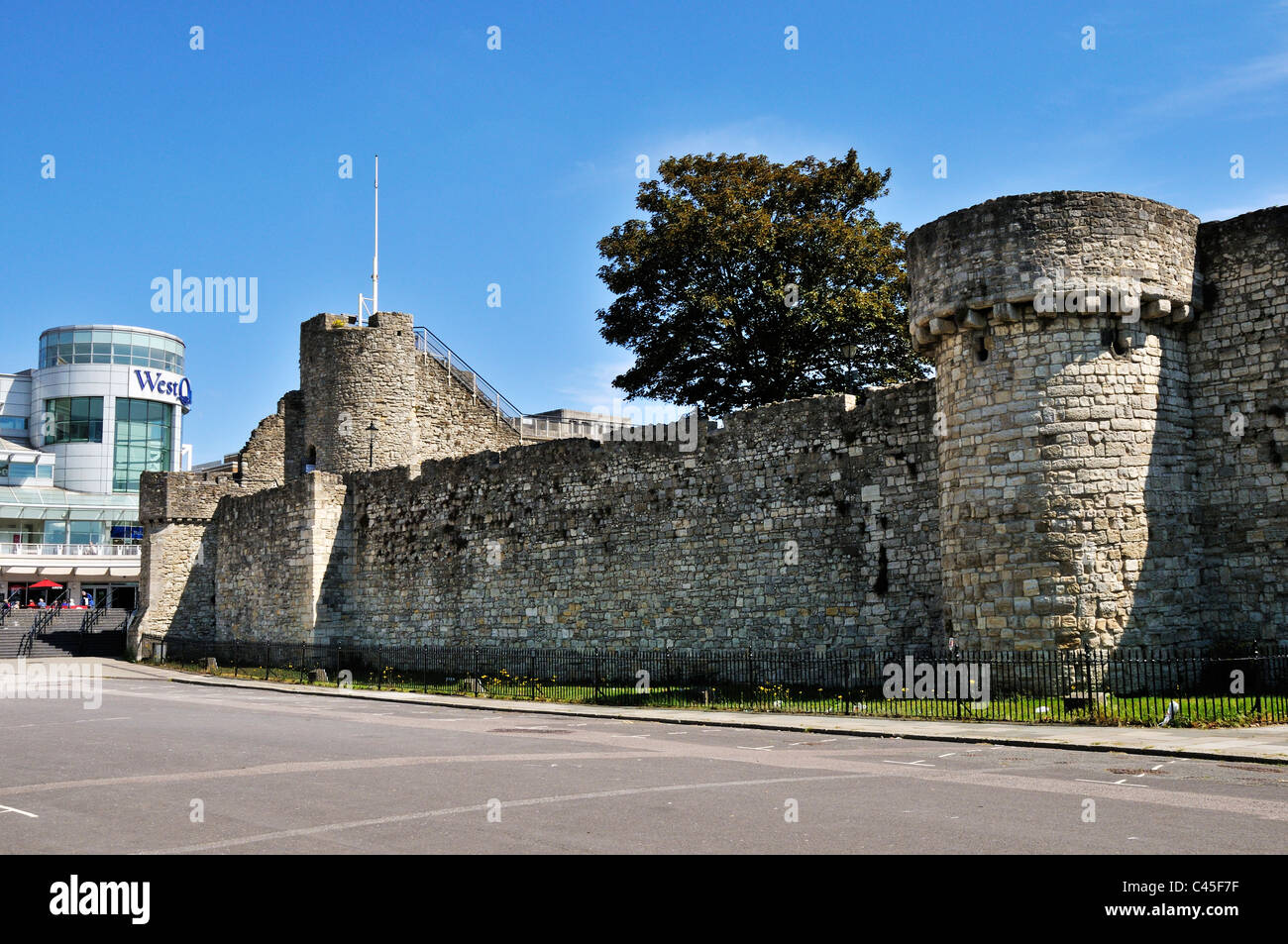 The defensive walls and towers of the medieval town of Hampton in front of the modern shopping centre of West Quay, - Stock Image