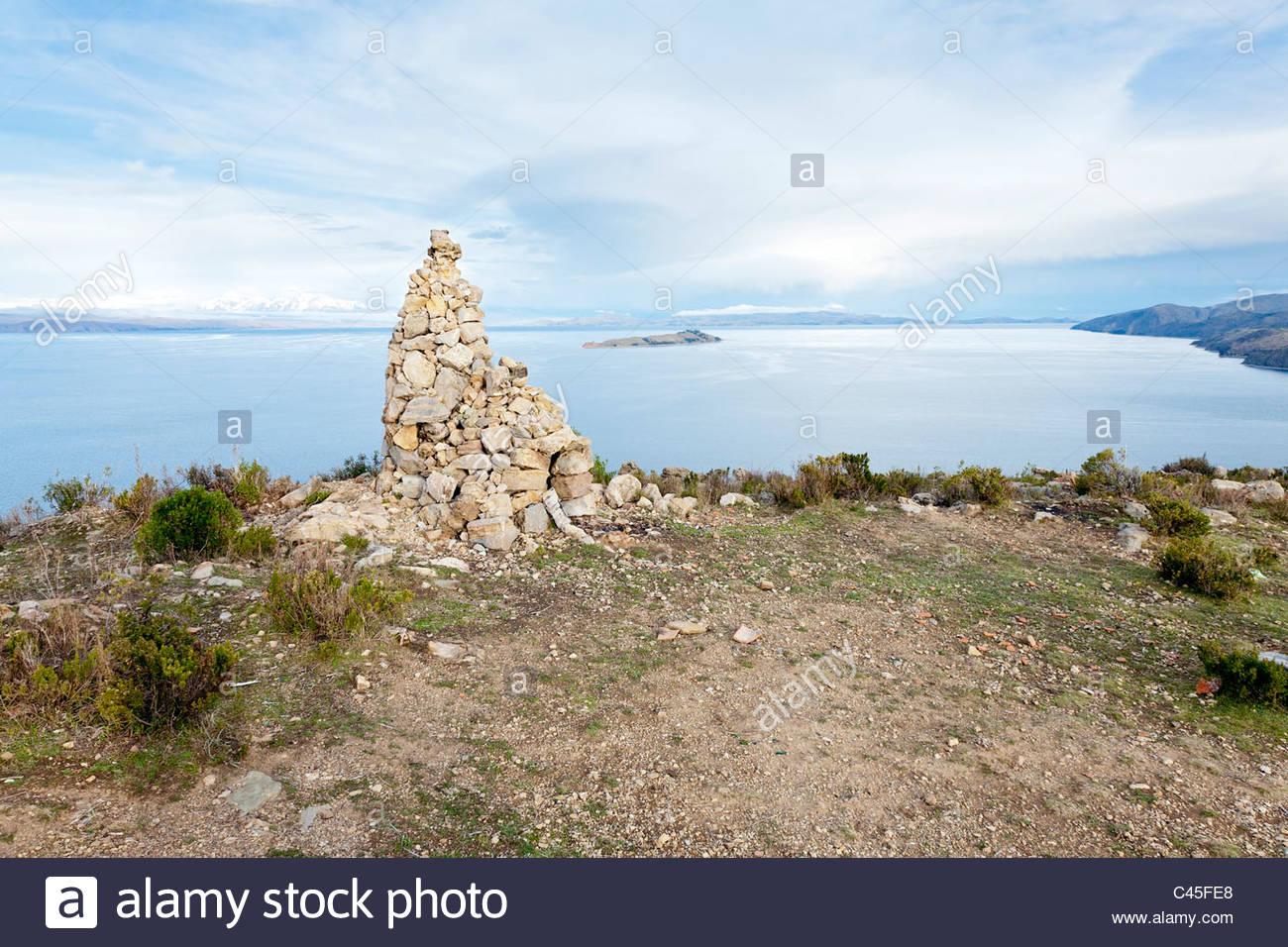 Stone cairn with Cordillera Real and Isla de la Luna in background. Isla del Sol, Lake Titicaca, La Paz Department, - Stock Image