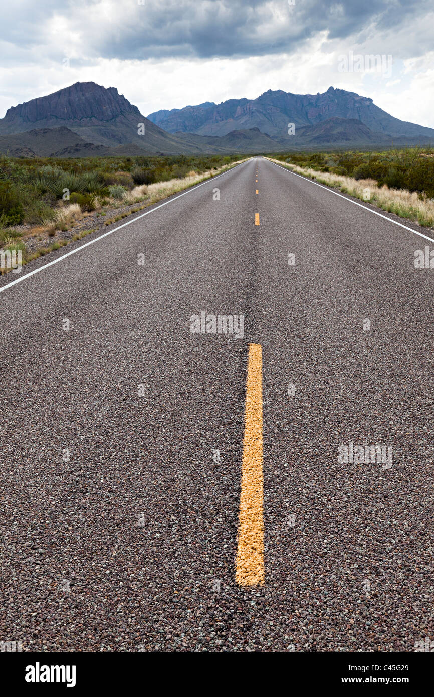Open road leading to mountains with dark clouds Big Bend National Park Texas USA - Stock Image