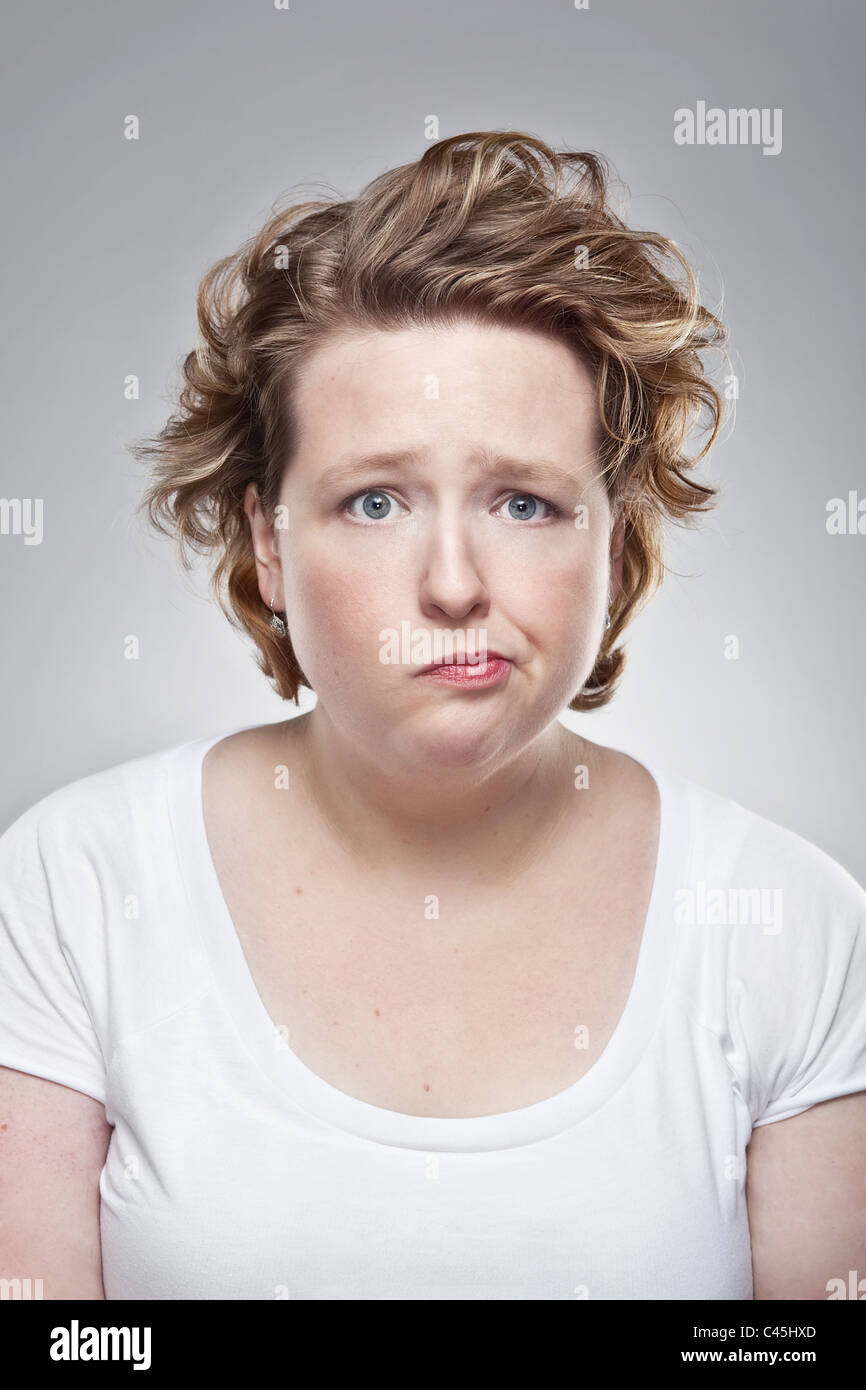 A studio portrait of a quirky overweight young woman having a bad hair day. She has a dejected but humorous expression. Stock Photo