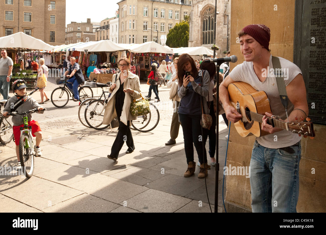 People watching a busker singing with guitar, the Market Square, Cambridge UK - Stock Image