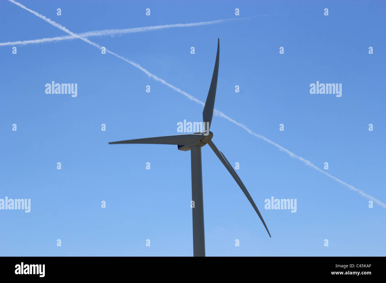 Wind power with airplane wakes in the blue sky - Stock Image