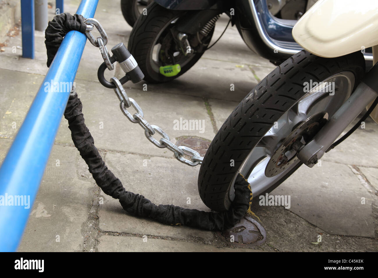 A parked scooter securely chained on a U.K. street. Stock Photo