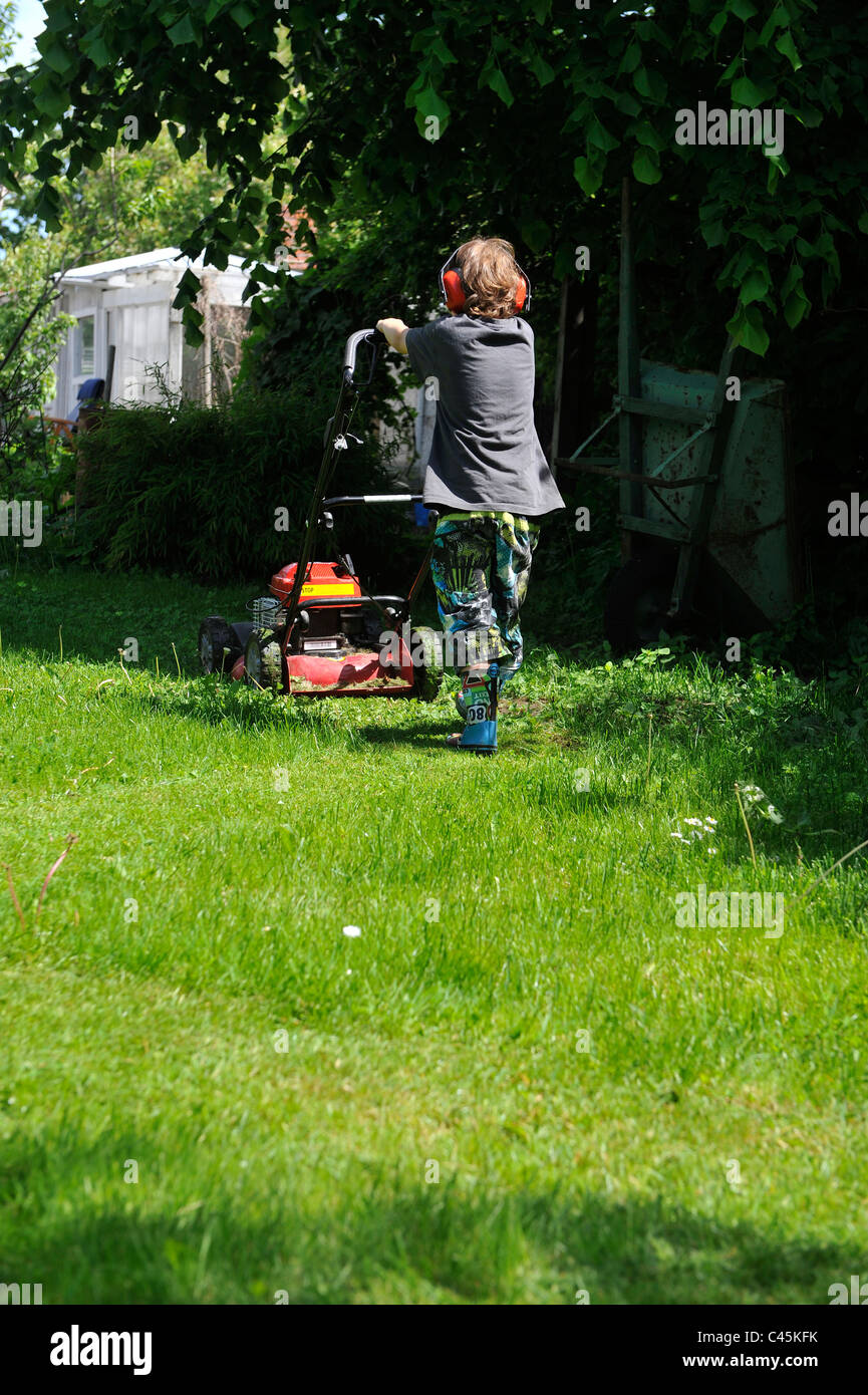 young boy cutting grass with a lawn mover - Stock Image