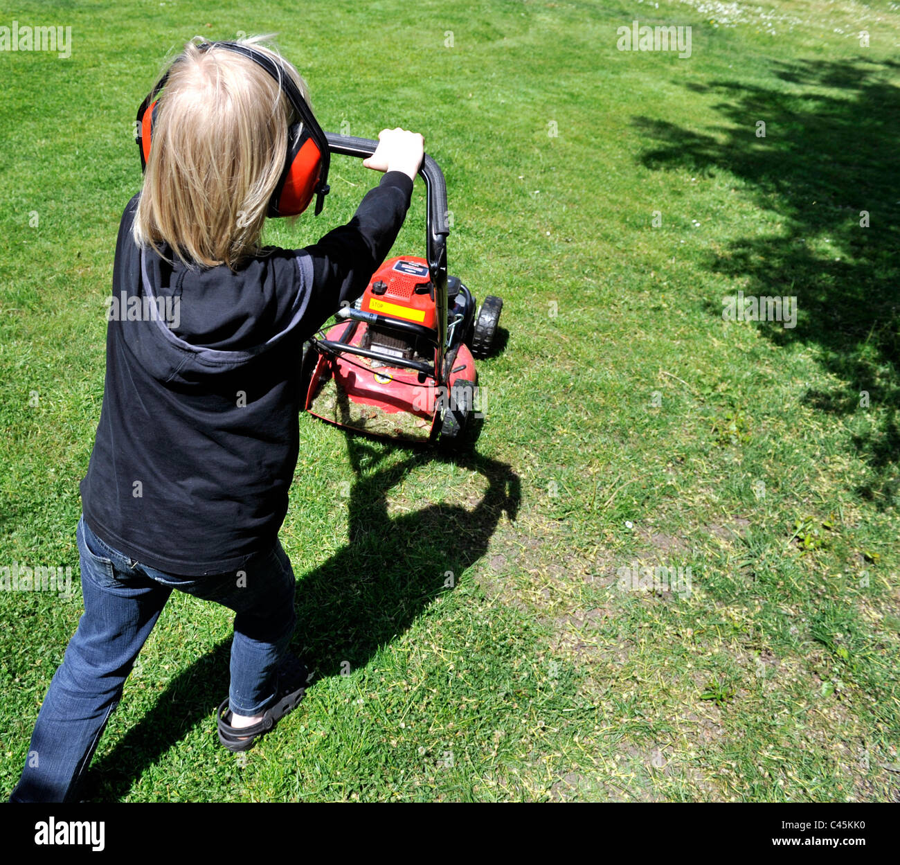 Blond boy cutting grass with a lawn mover - Stock Image