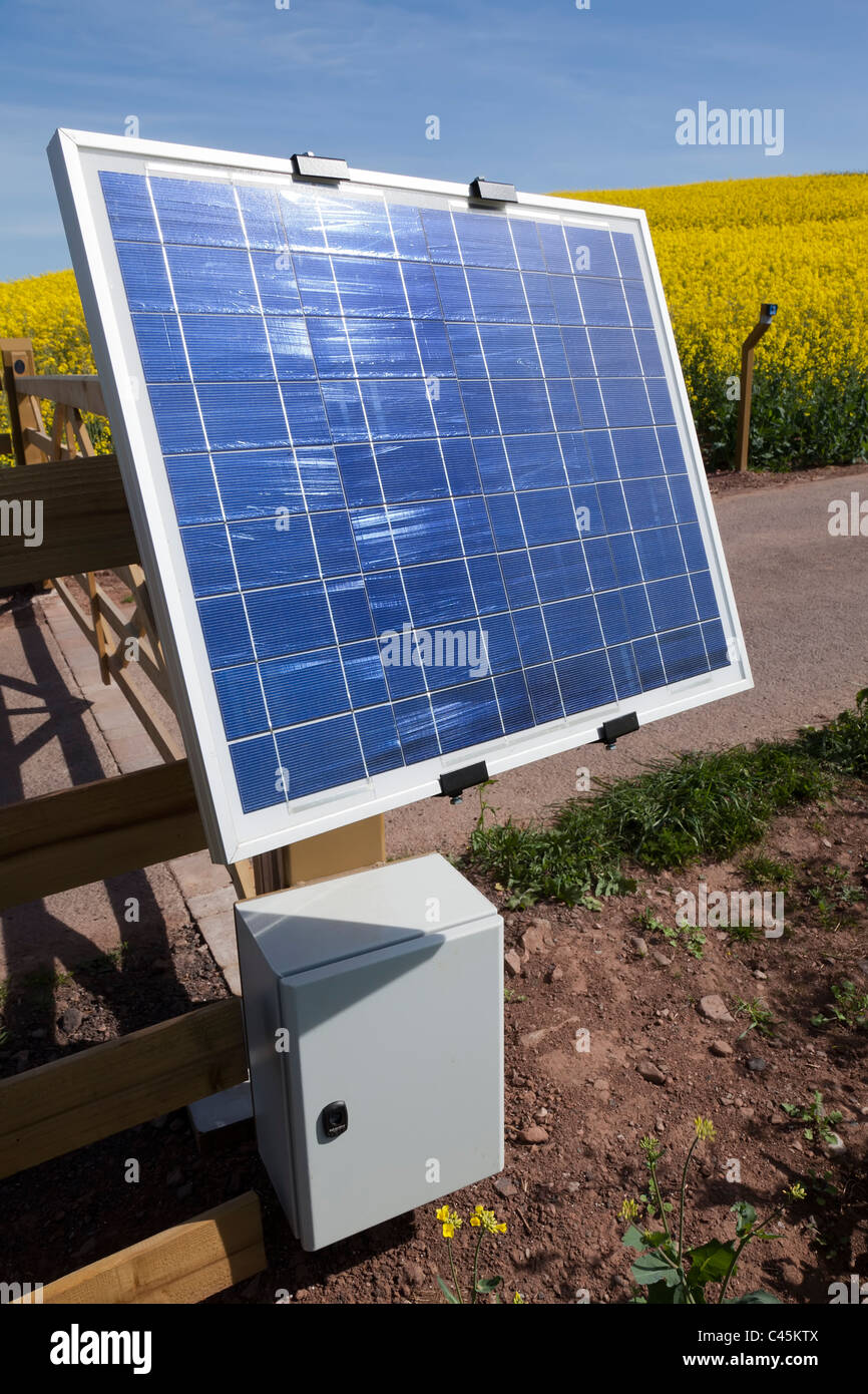 Solar powered gate opener control on a farm with the control post in the distance Wales UK - Stock Image