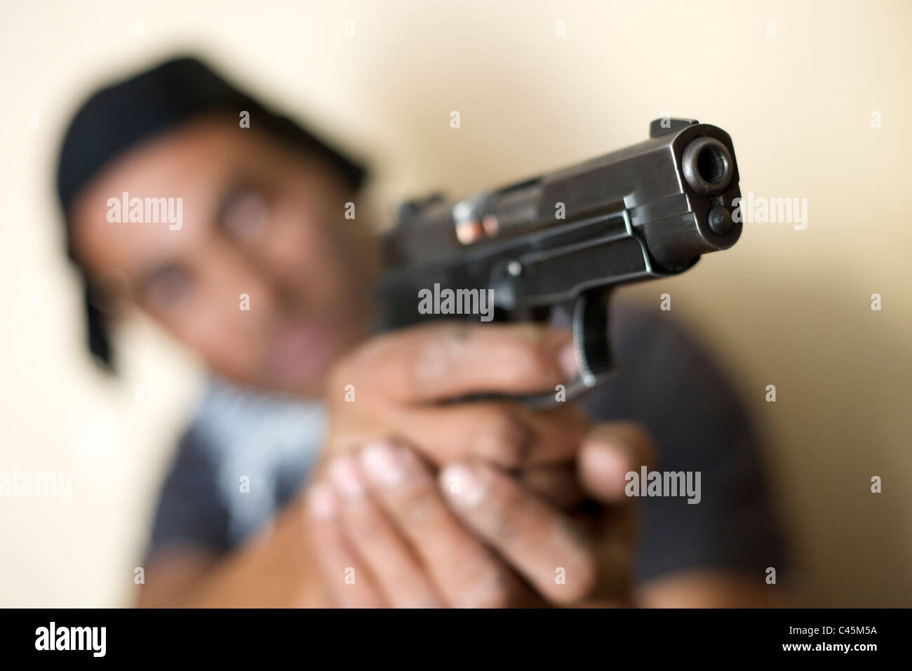 A man with a baseball cap pointing a pistol just off camera. - Stock Image