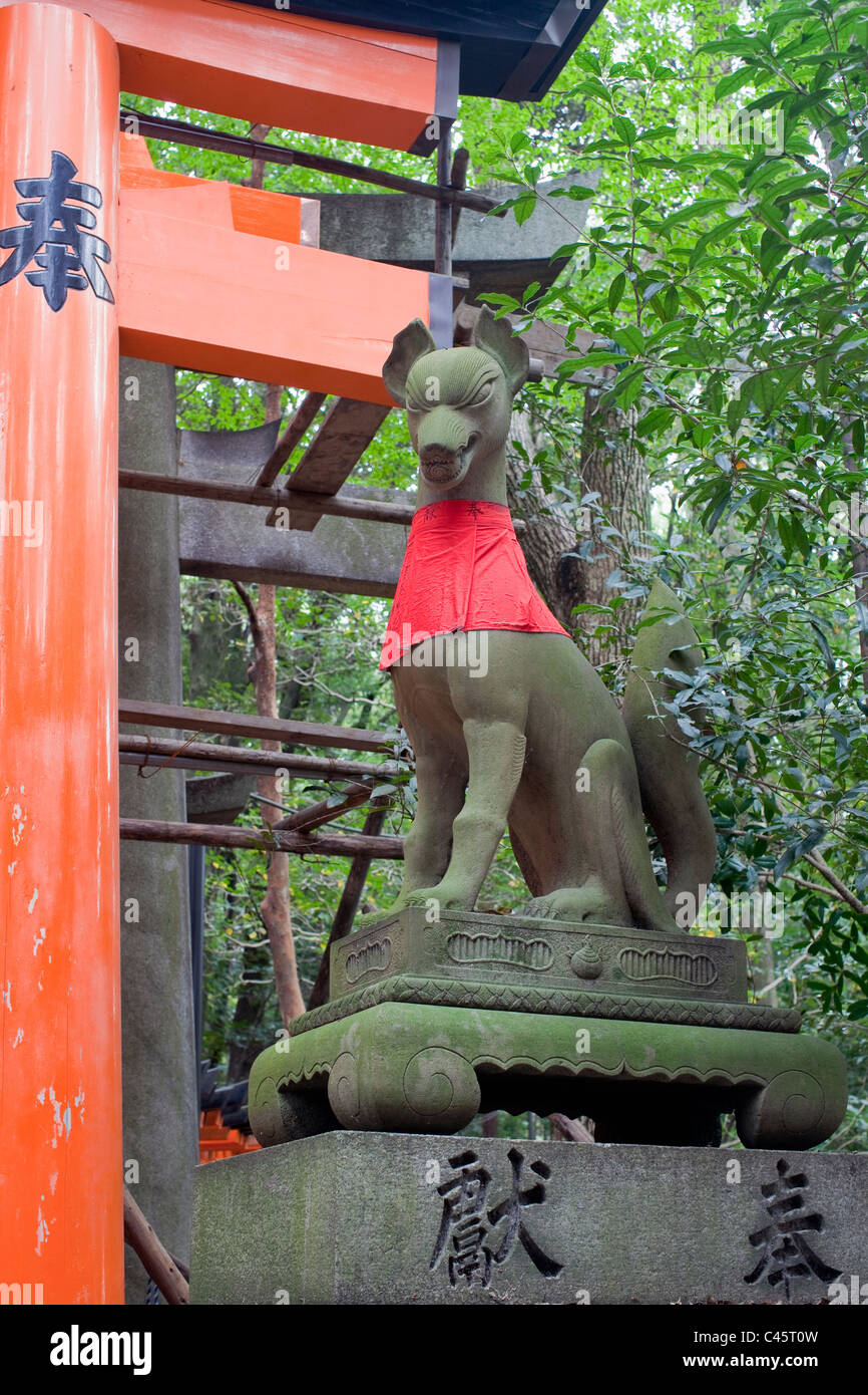 Red-bibbed fox statue and part of orange torii gate at Fushimi-Inari Taisha shrine, Kyoto, Japan. - Stock Image