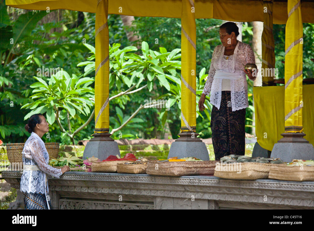 Women bring offerings at PURA TAMAN SARASWATI during the GALUNGAN FESTIVAL - UBUD, BALI, INDONESIA - Stock Image