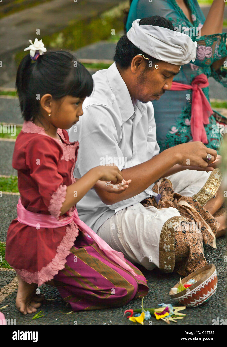 Father and daughter pray at PURA TAMAN SARASWATI during the GALUNGAN FESTIVAL - UBUD, BALI, INDONESIA - Stock Image
