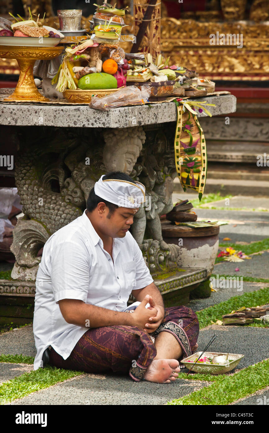 A Hindu man prays at PURA TAMAN SARASWATI during the GALUNGAN FESTIVAL - UBUD, BALI, INDONESIA - Stock Image