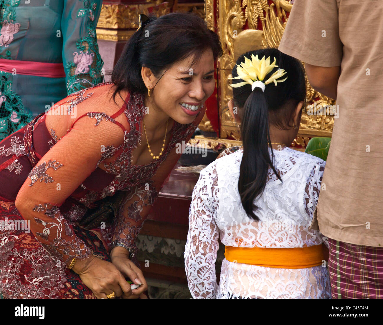BALINESE WOMAN and daughter at PURA TAMAN SARASWATI during the GALUNGAN FESTIVAL - UBUD, BALI, INDONESIA - Stock Image
