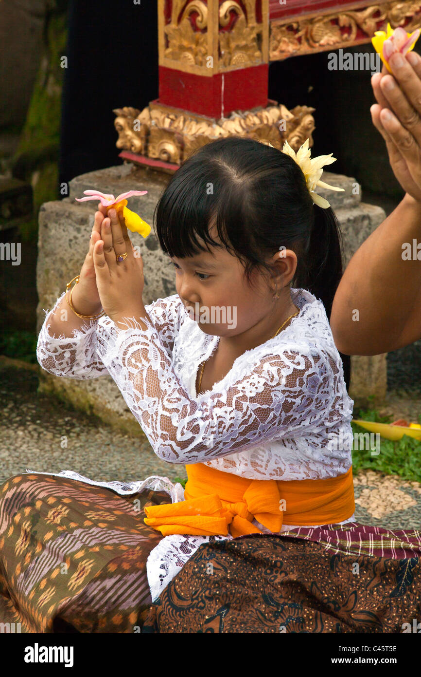 A daughter prays at PURA TAMAN SARASWATI during the GALUNGAN FESTIVAL - UBUD, BALI, INDONESIA - Stock Image