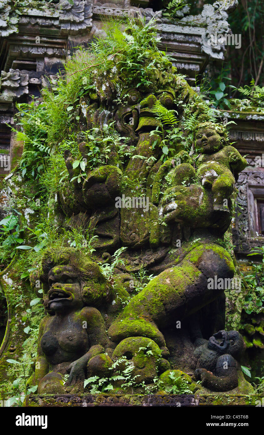 Moss and ferns grow on a Hindu statue at PURA TAMAN SARASWATI - UBUD, BALI, INDONESIA - Stock Image