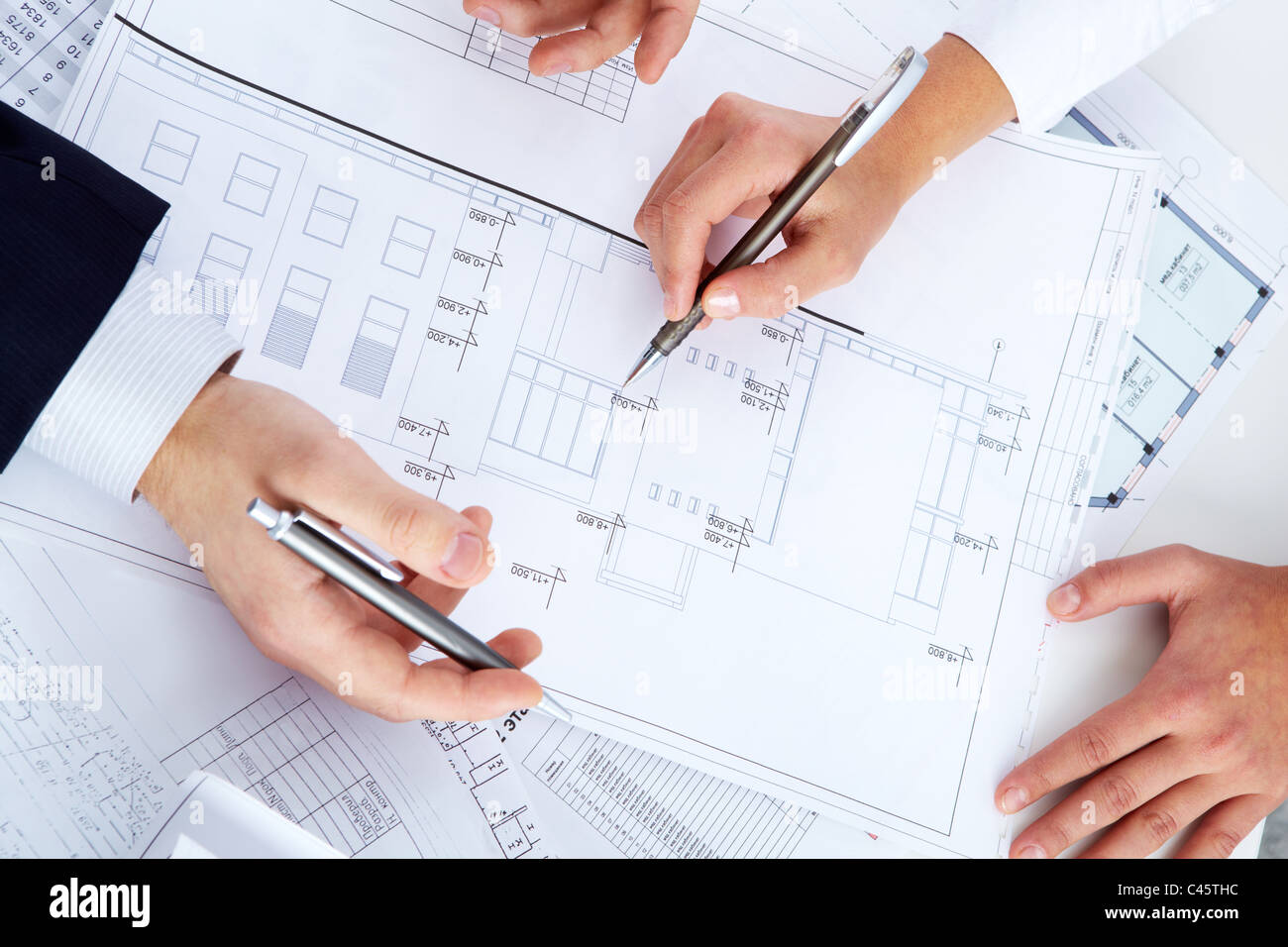 Close-up of engineers hands with pens over blueprints with sketches of projects - Stock Image