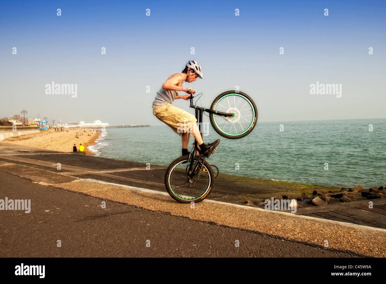 young man doing wheelie tricks stunts on his BMX bike - Stock Image