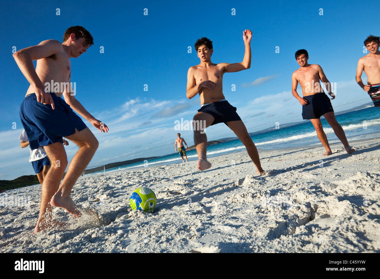 Young men playing beach football. Goode Beach, Frenchman Bay, Albany, Western Australia, Australia - Stock Image