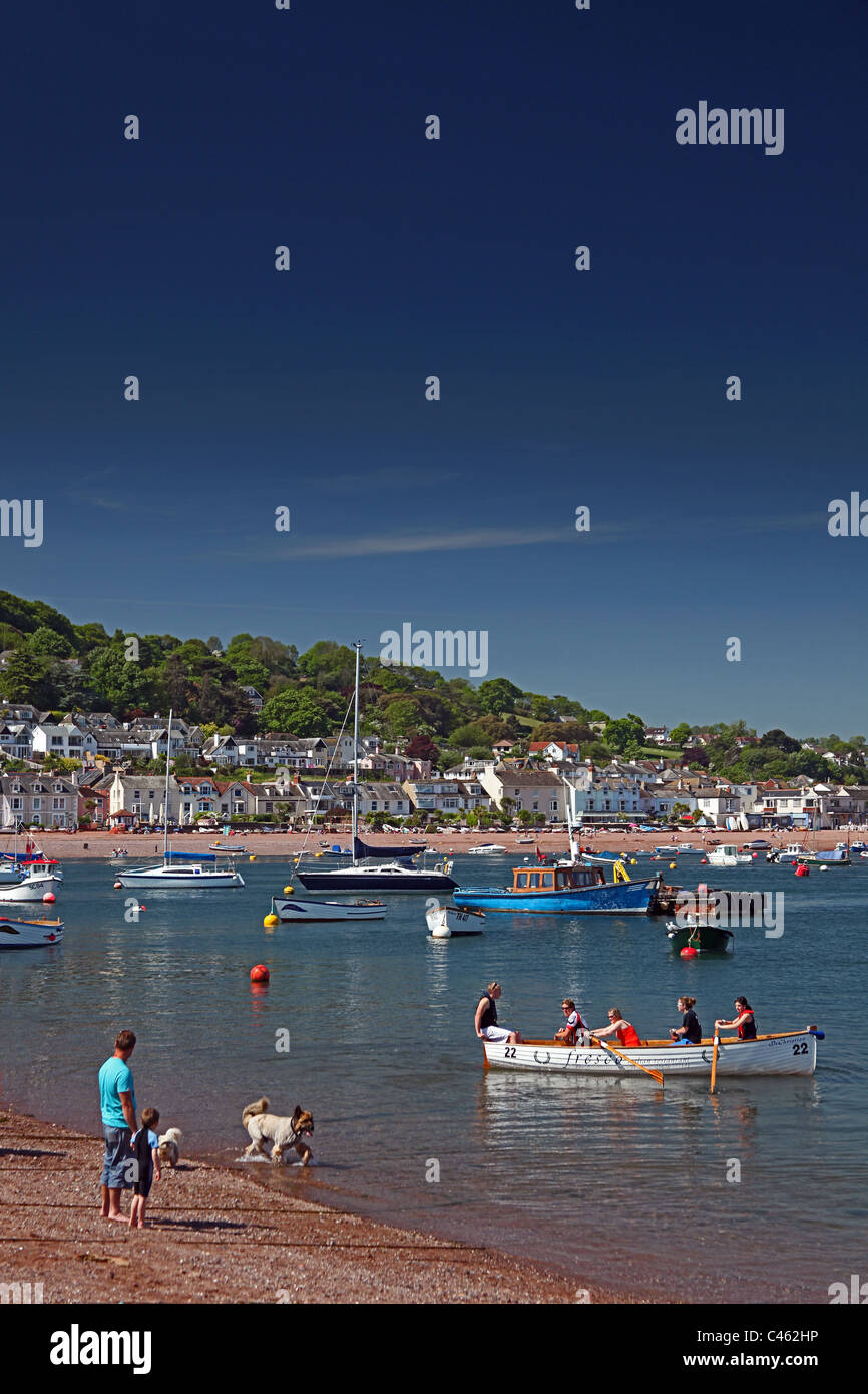 A father and son watch a rowing gig leaving Teignmouth on the River Teign estuary with Shaldon beyond, Devon, England, - Stock Image