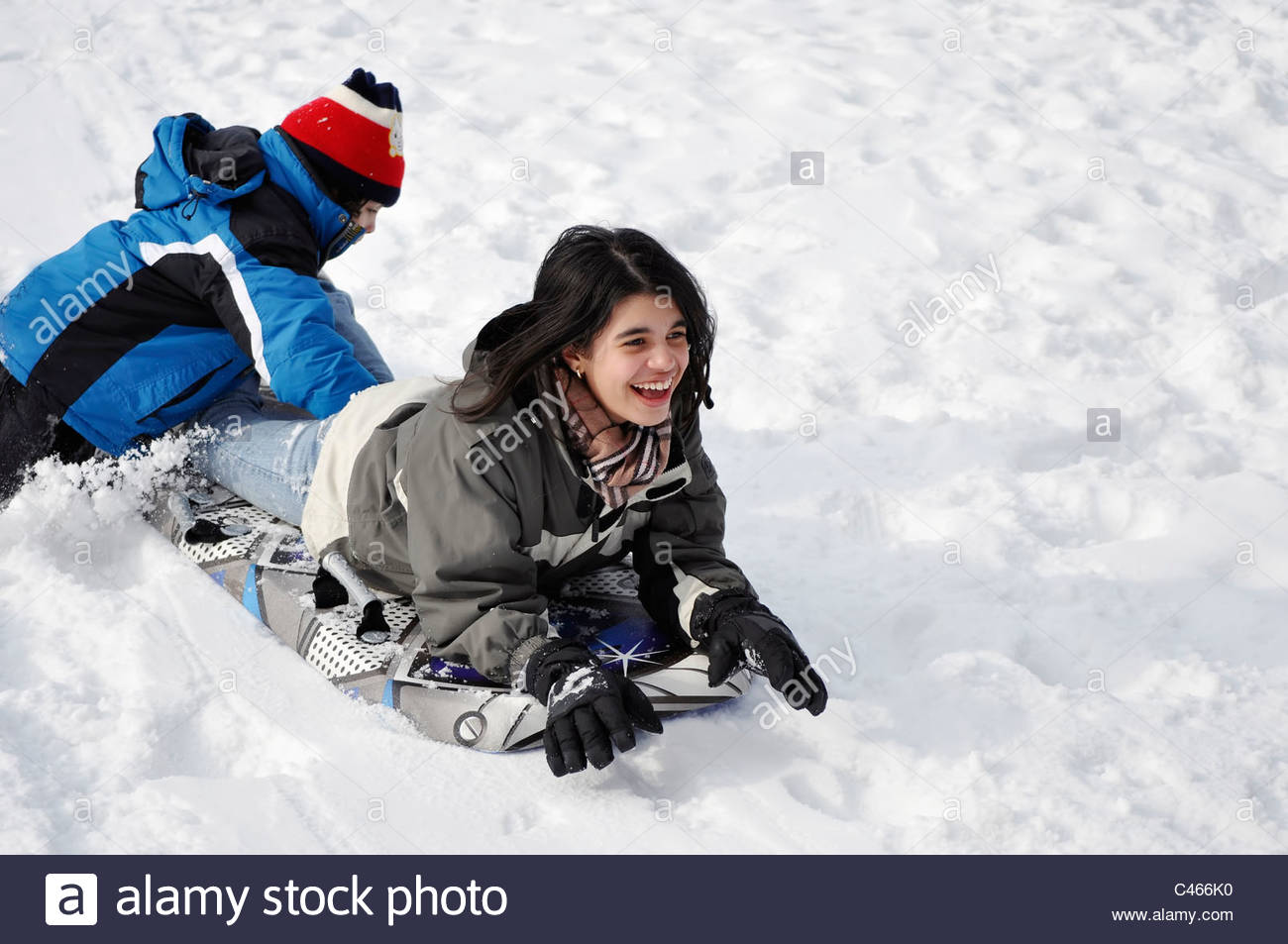 Hispanic children sliding in the snow during the Canadian winter. Playing and having fun outdoors. Stock Photo
