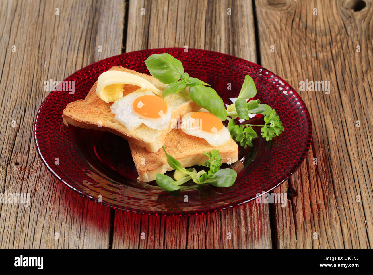 Fried eggs on slices of toasted bread - Stock Image