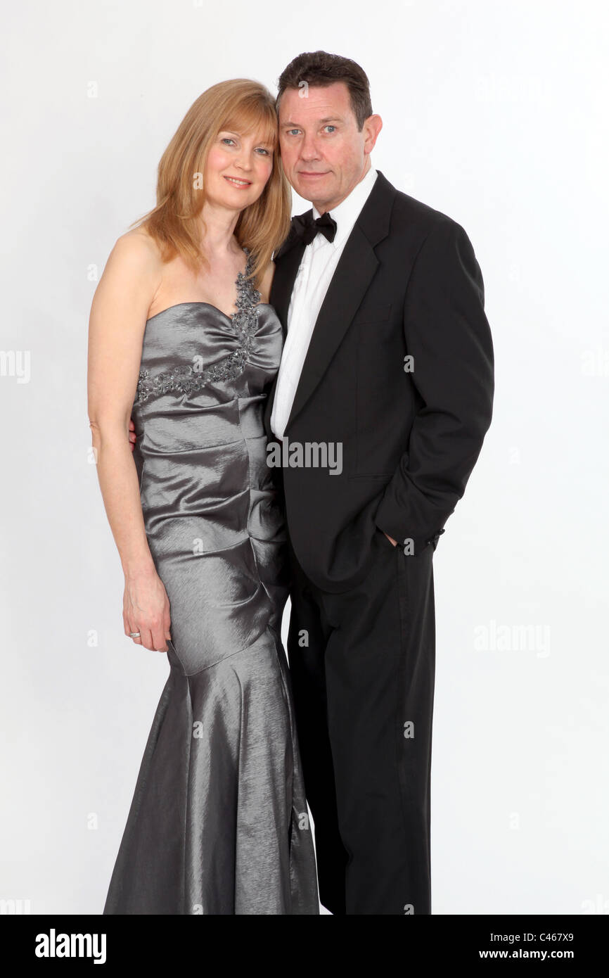 Couple wearing smart evening dress and suit with bow tie. - Stock Image