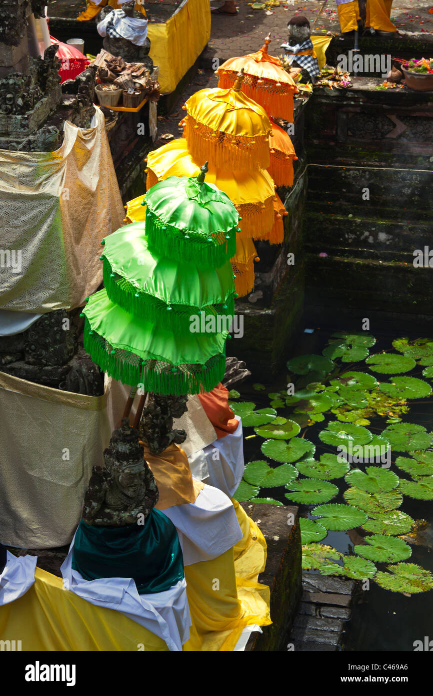 Colored umbrellas at the PURA BEJI in the village of Mas during the GALUNGAN FESTIVAL - UBUD, BALI, INDONESIA - Stock Image