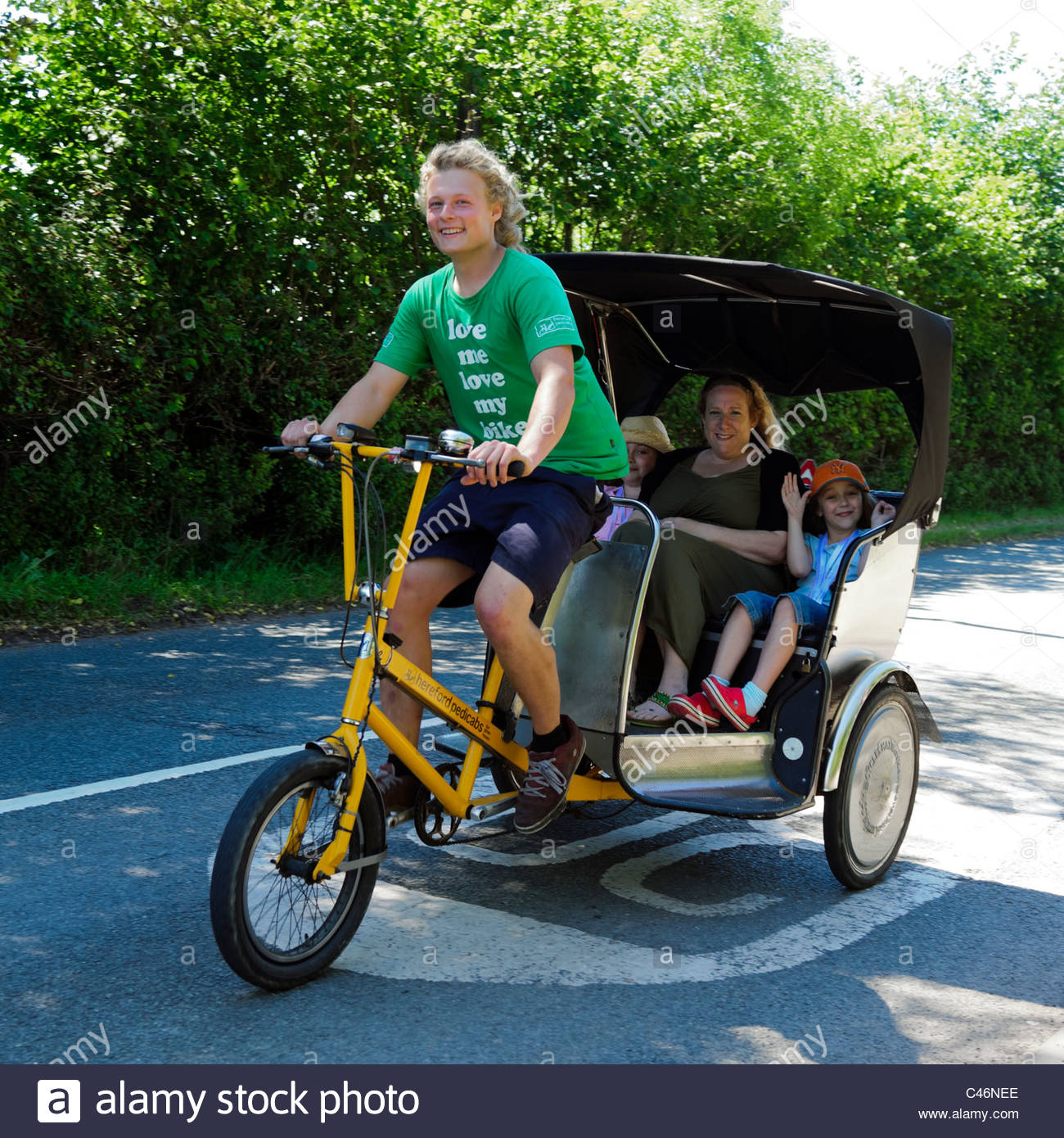 Hay on Wye, Wales, UK. Hay festival pedicab taking woman & children to town center. - Stock Image