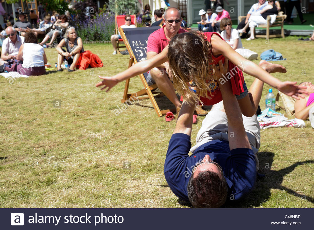 Hay on Wye, Wales, UK. Hay festival father playing with daughter on grass. - Stock Image