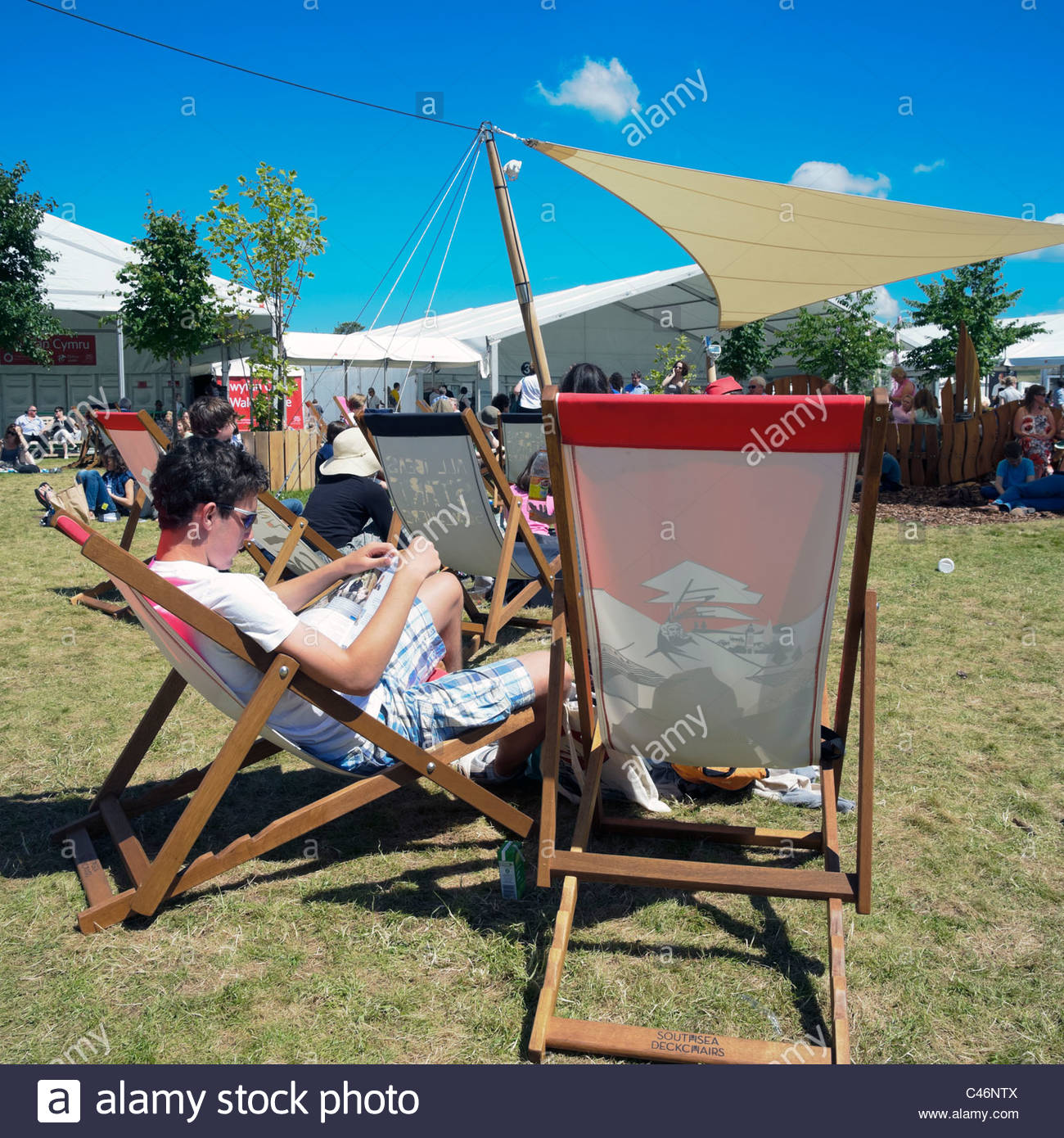Hay on Wye, Wales, UK. Hay festival man reading a book sitting in a deckchair. - Stock Image