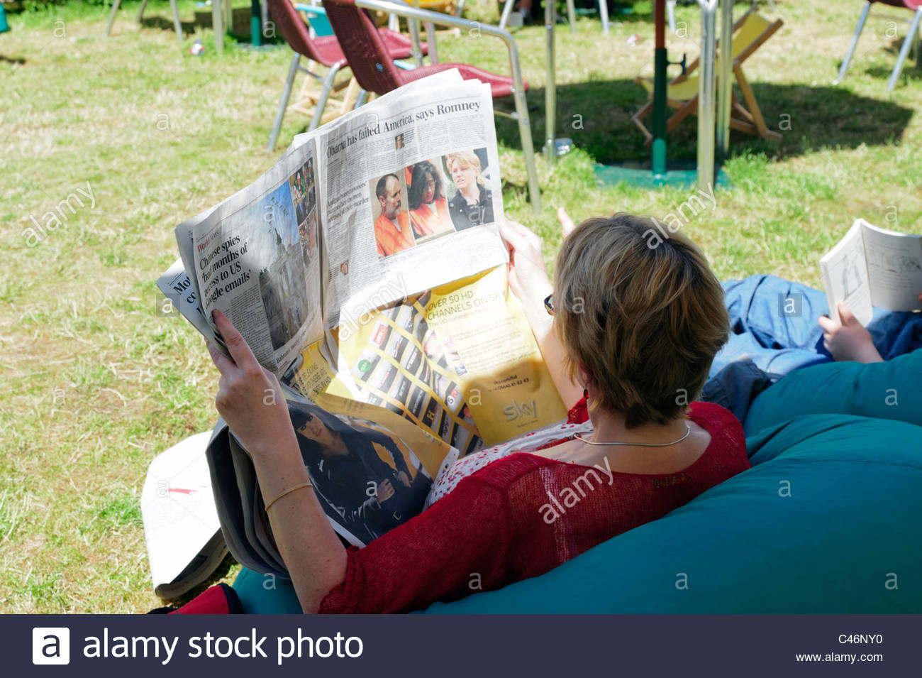 Hay on Wye, Wales, UK. Hay festival woman sitting on bean bag reading a newspaper. Stock Photo