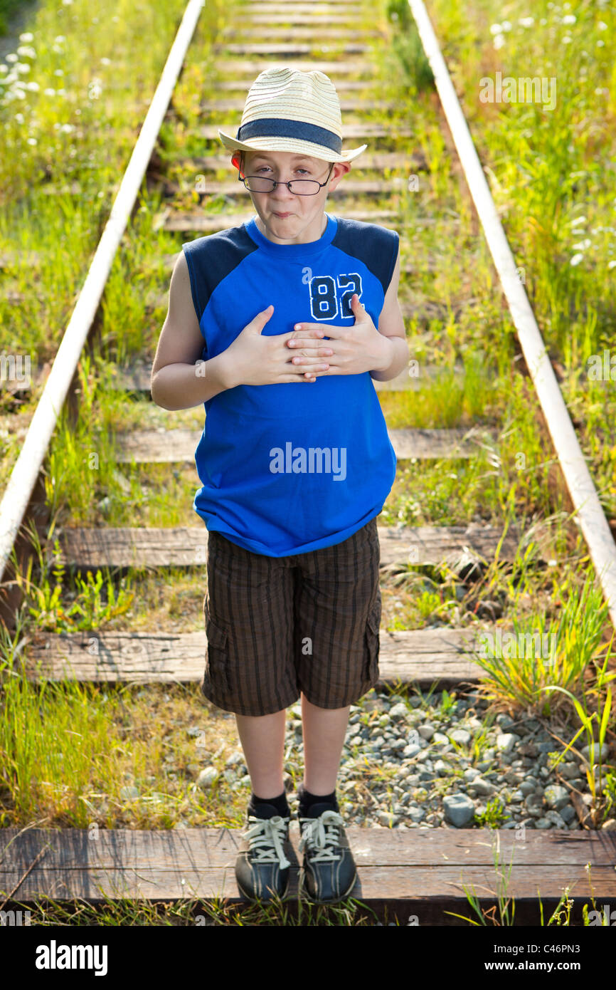 A boy making a funny face on train tracks. - Stock Image