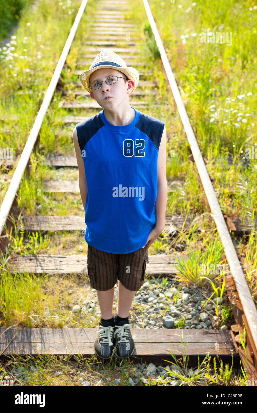 A boy standing defiantly on train tracks. - Stock Image
