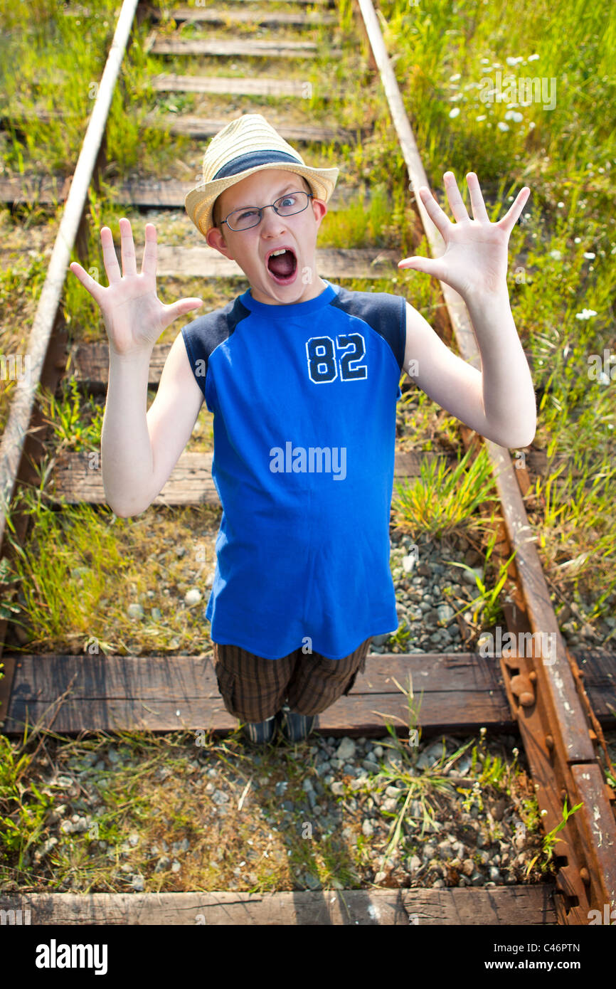 A frightened boy on train tracks. - Stock Image