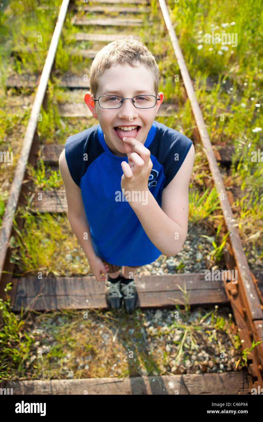 A boy on train tracks, holding his tongue. - Stock Image