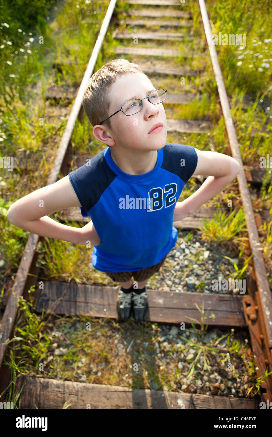 A boy posing on train tracks. - Stock Image