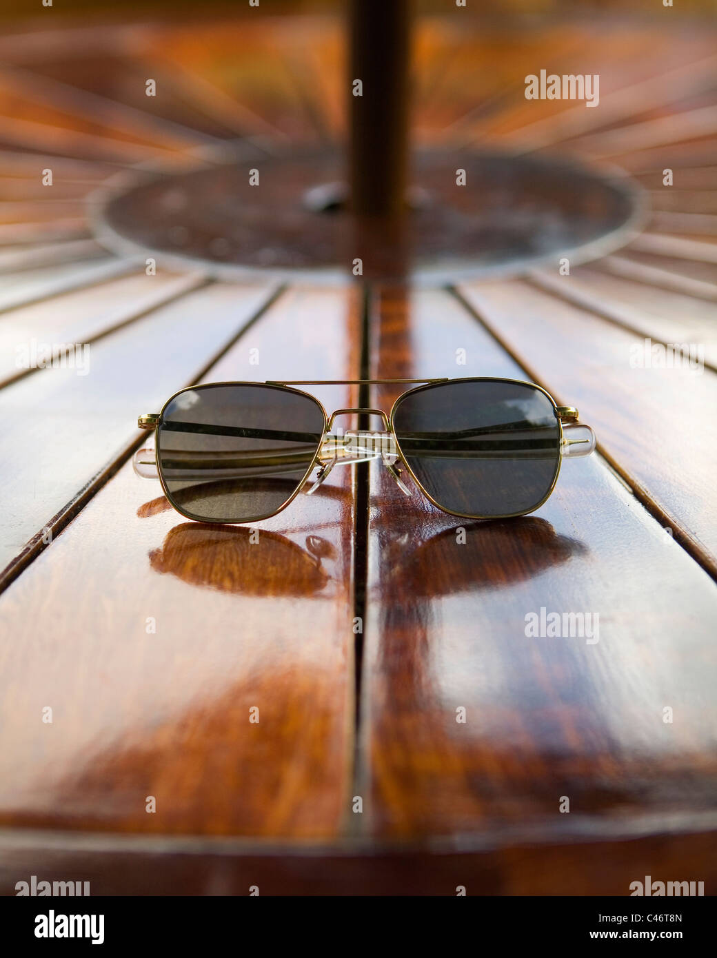 A pair of aviator sunglasses sit on a wooden table - Stock Image