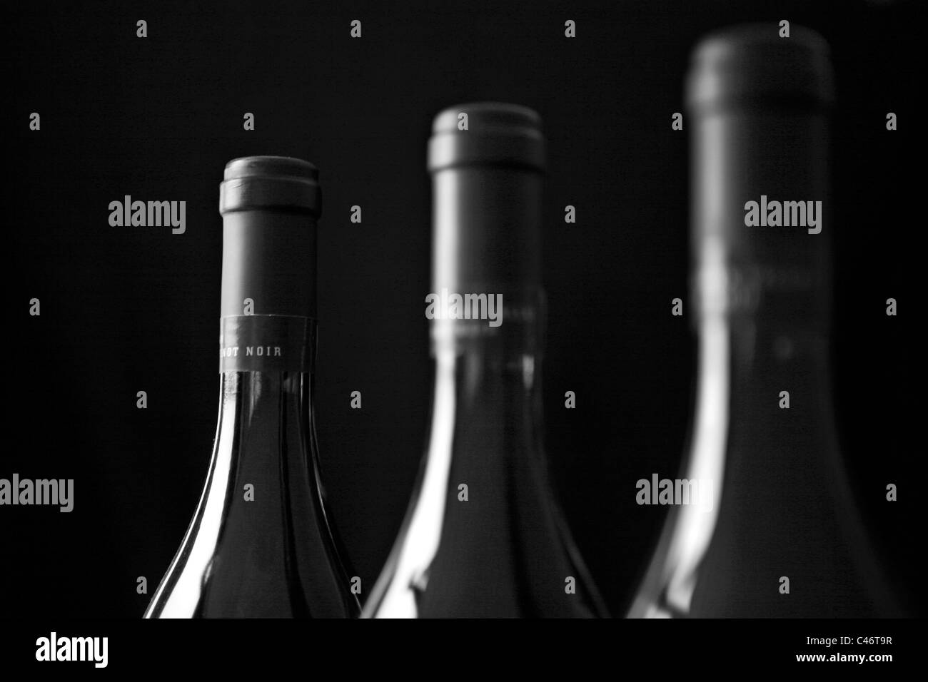 Three bottles of wine placed in a row. - Stock Image