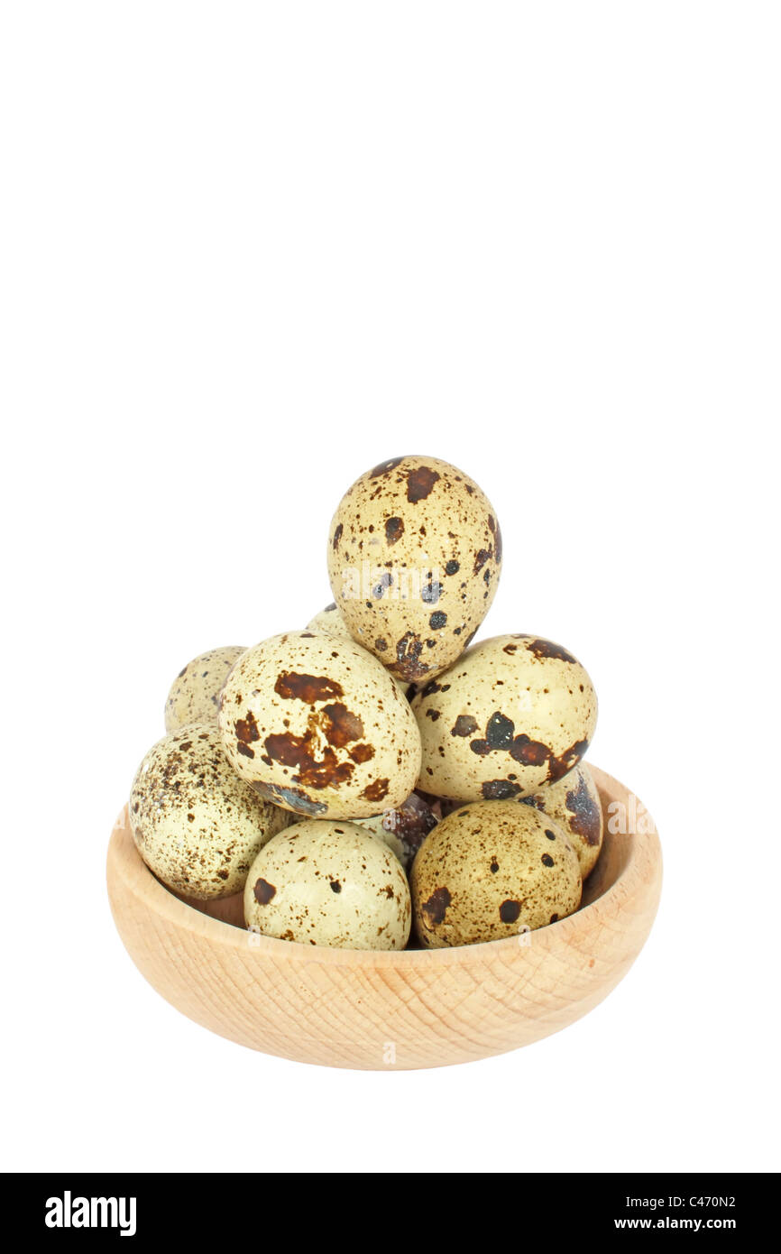 Eggs of Japanese quail in wooden bowl isolated on white - Stock Image