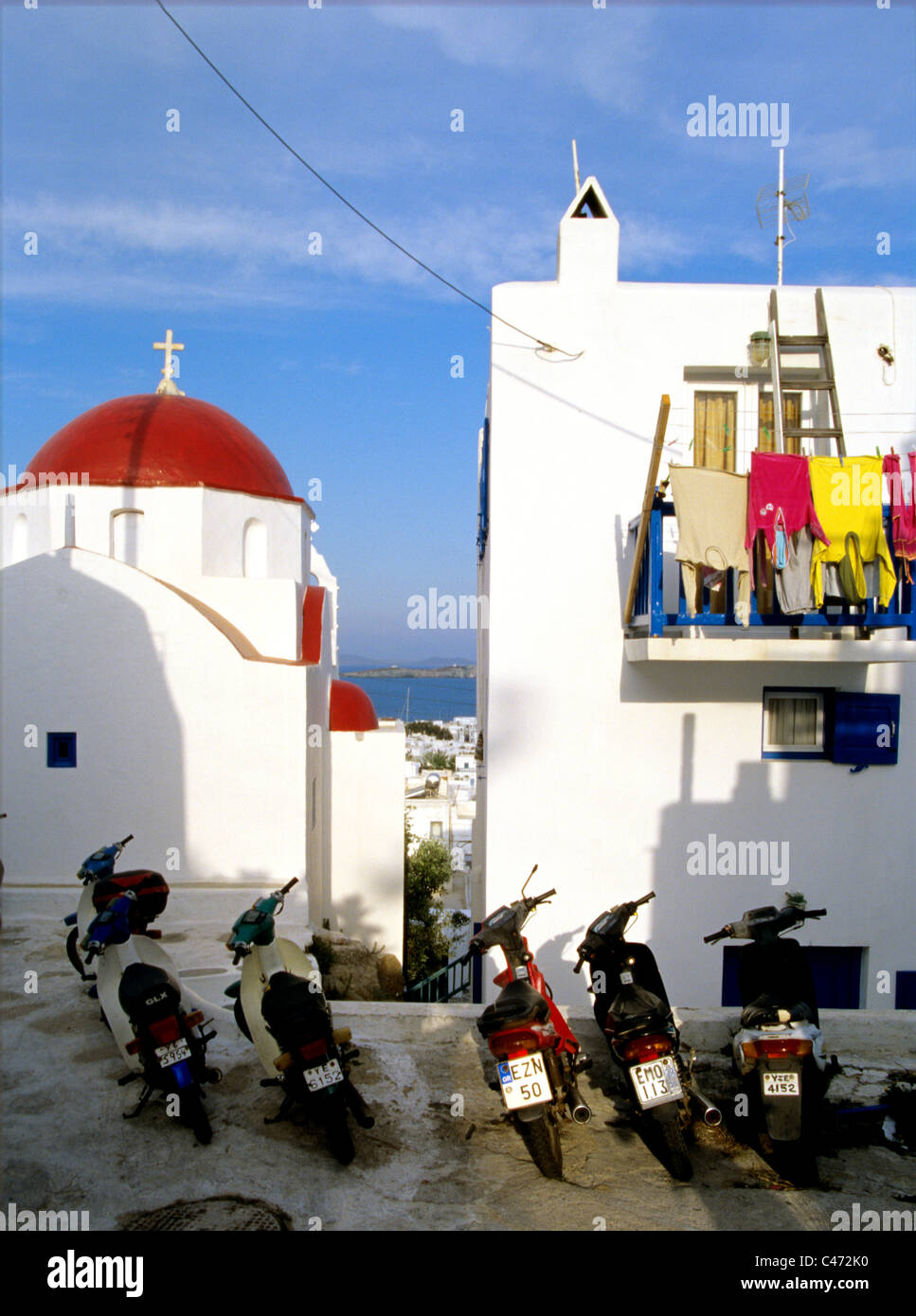 laundry hangs on porch above parked motor scooters in old town of Mykonos Greece - Stock Image