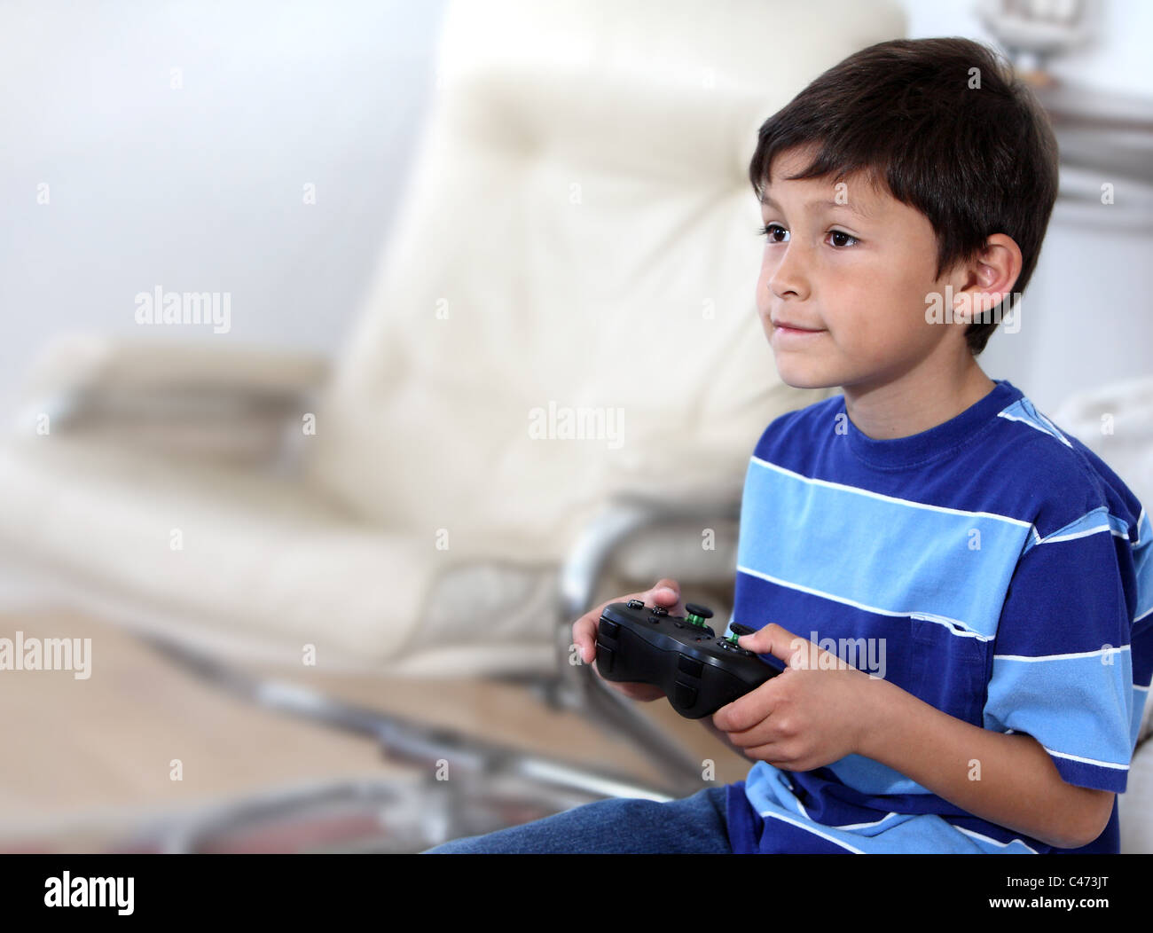 Young hispanic or Latino boy playing with a video game - with copy space to left - Stock Image