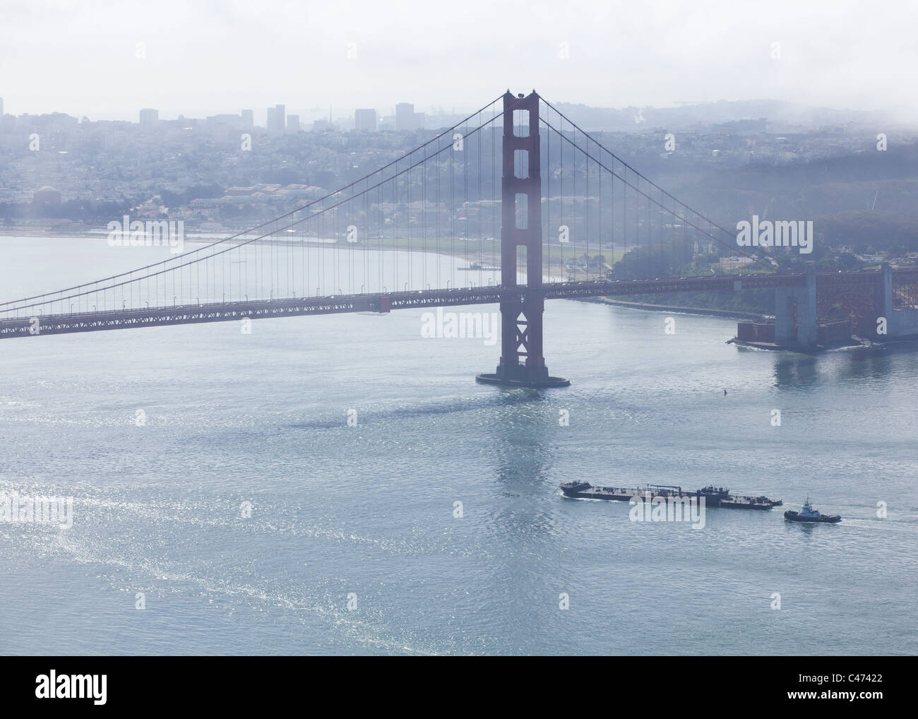 A freight barge makes way into the San Francisco bay under foggy sky - Stock Image