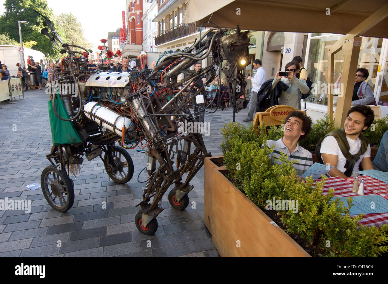 A mechanical horse amuses two young male tourists as part of the street theatre for the 2011 Brighton Festival Fringe - Stock Image